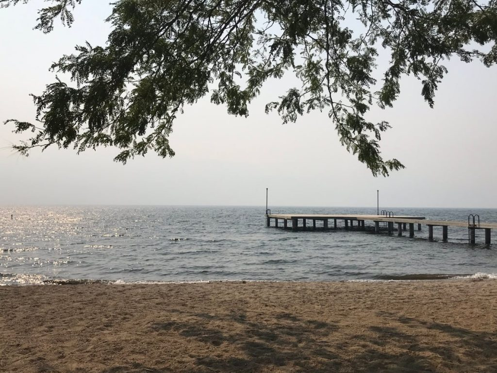A photograph of a West Kelowna beach during the daytime taken September 8 2020. The sky is visibly smokey, completely grey with no visible horizon. The sunlight reaching the beach looks darker than normal and red-shifted because of the smoke.