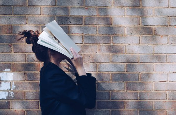 Woman with Book in front of natural rustic red brick background holding book up to her face.