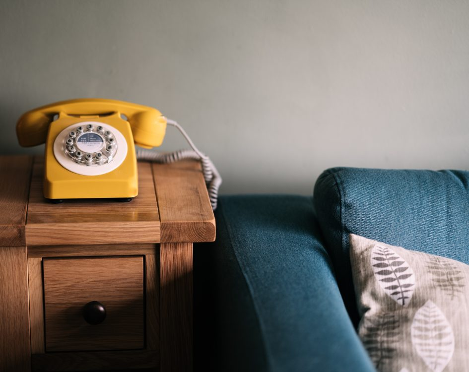 A yellow rotary telephone sits on a coffee table next to a blue couch.